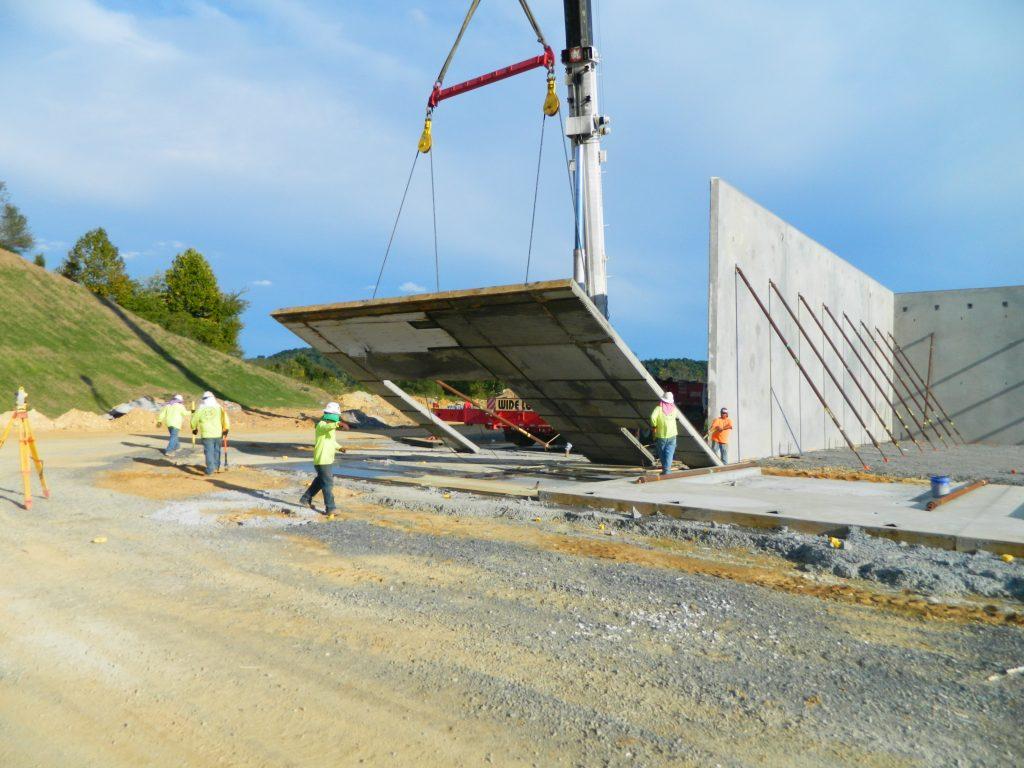 Eldridge Concrete crane lifting tilt up wall into place for MHC Kenworth